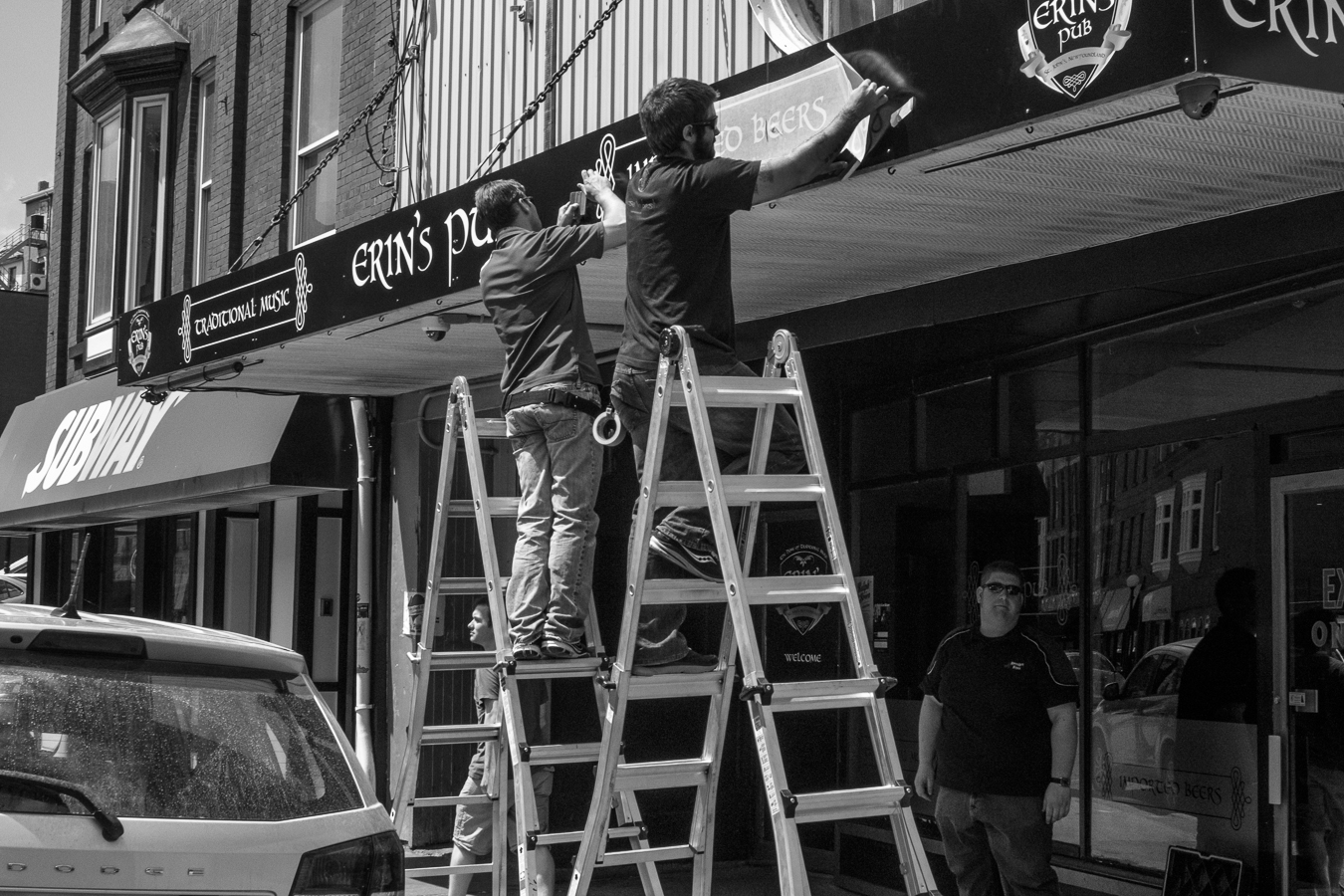 Sign workers installing new lettering. - Erins Pub - Water Street