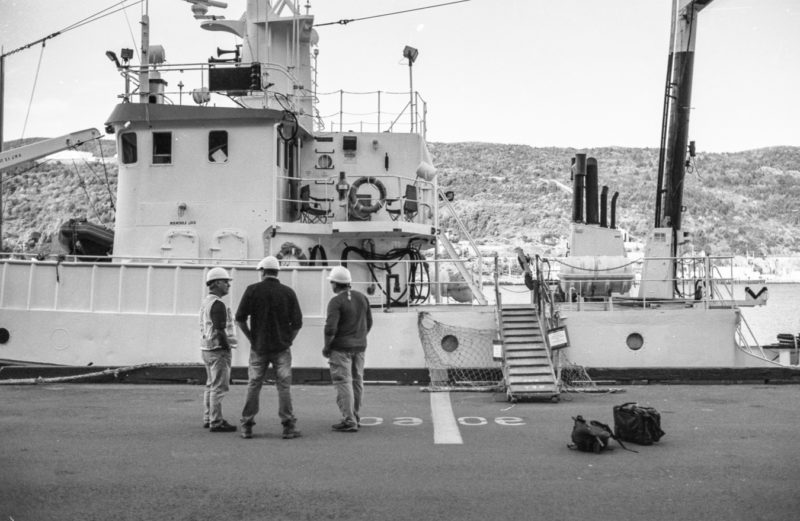 Gentlemen getting ready to board a ship in the harbour - harbour apron