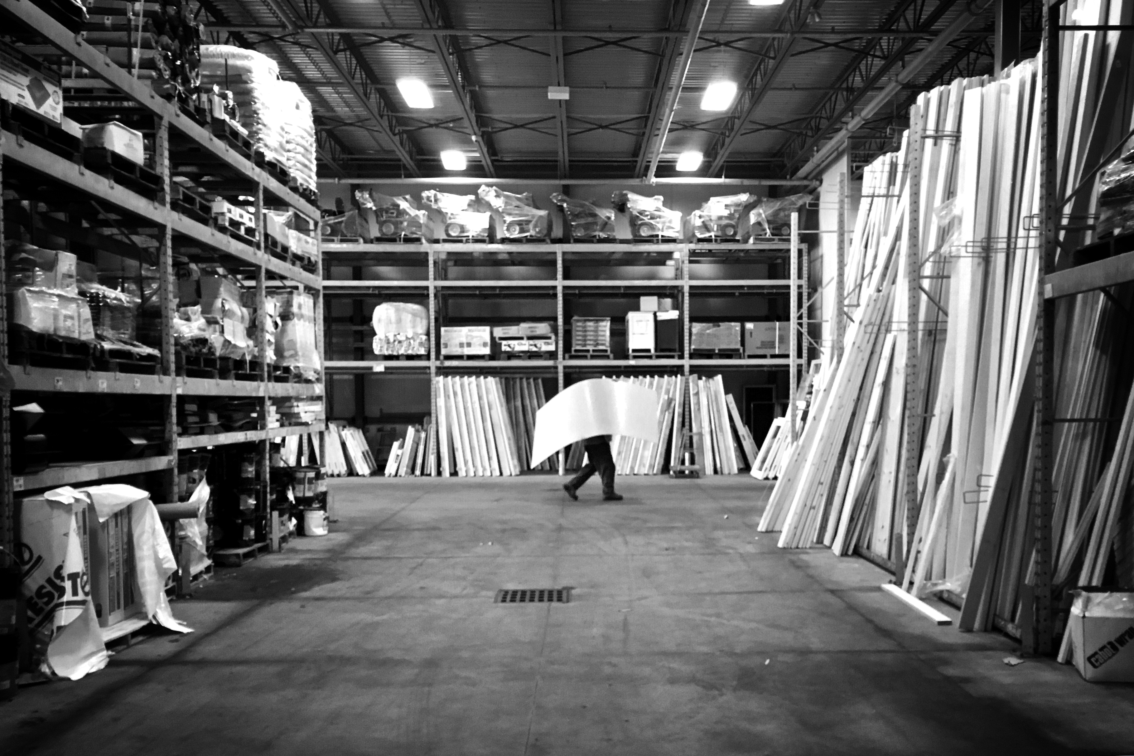 A worker walking a sheet of pegboard to a customer - Rona warehouse - Torbay Road